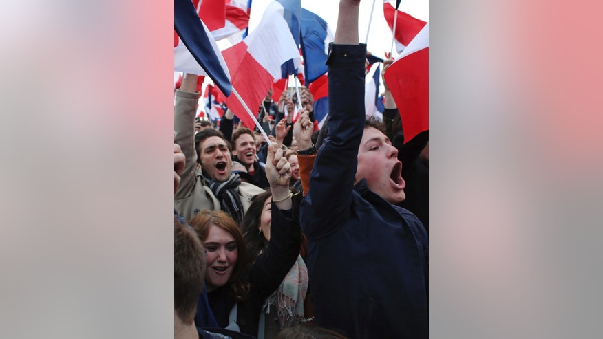 Supporters of French independent centrist presidential candidate, Emmanuel Macron celebrate outside the Louvre museum in Paris, France, Sunday, May 7, 2017. Polling agencies have projected that centrist Emmanuel Macron will be France's next president, putting a 39-year-old political novice at the helm of one of the world's biggest economies and slowing a global populist wave. The agencies projected that Macron defeated far-right leader Marine Le Pen 65 percent to 35 percent on Sunday. (AP Photo/Thibault Camus)
