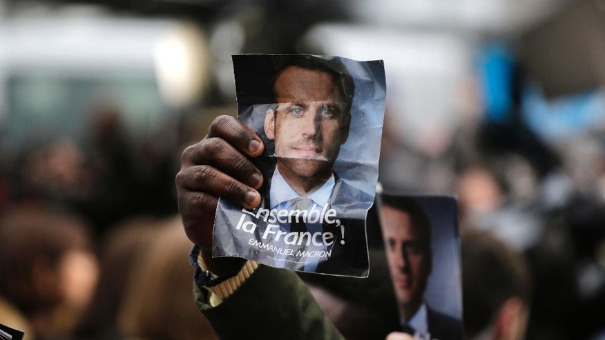 Supporters of French independent centrist presidential candidate, Emmanuel Macron hold up his photo outside his campaign headquarters in Paris, France, Sunday, May 7, 2017. Polling agencies have projected that centrist Emmanuel Macron will be France's next president, putting a 39-year-old political novice at the helm of one of the world's biggest economies and slowing a global populist wave. The agencies projected that Macron defeated far-right leader Marine Le Pen 65 percent to 35 percent on Sunday. (AP Photo/Emilio Morenatti)