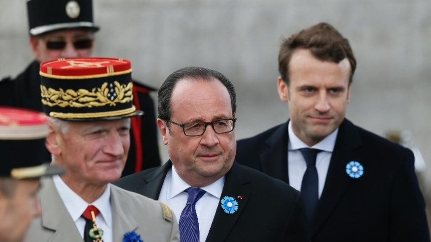 Current French President Francois Hollande, center, is joined by French president-elect Emmanuel Macron, right, during a ceremony to mark Victory Day in Paris, France, Monday, May 8, 2017. French president-elect Emmanuel Macron, will appear Monday alongside current President Francois Hollande in commemoration of the end of World War II. Monday, a national holiday, marks the day of the formal German defeat in World War II. (AP Photo/Francois Mori, Pool)