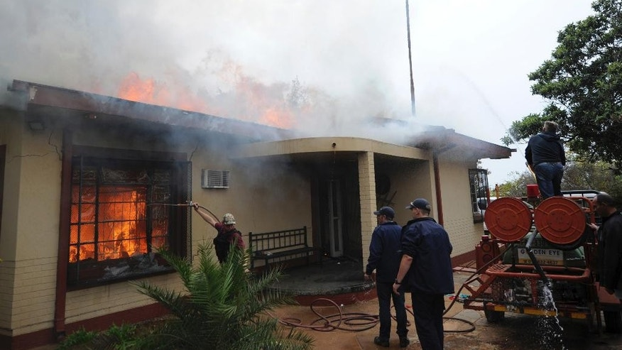 Firemen attempt to extinguish s fire at a  white residence in Coligny, South Africa, in the town where  two South Africa white farmers were released on bail by the magistrates court, Monday May 8, 2017. The two, who are accused of murdering a black teenager, were granted bail in the racially sensitive case that sparked racial violence. (AP Photo)