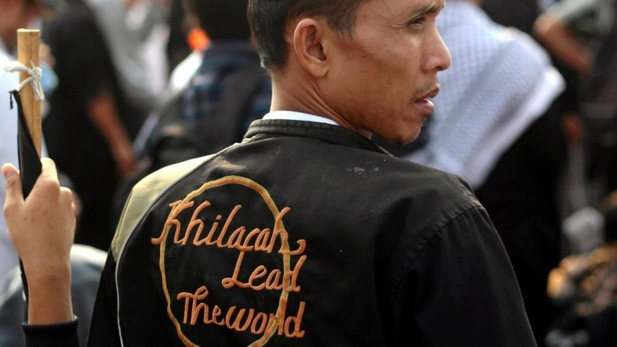 "FILE - In this Tuesday, Aug. 19, 2011 file photo, a member of Hizbut Tahrir Indonesia wears a jacket with embroidery that reads ""Caliphate leads the world"" during a rally outside the presidential palace in Jakarta. Indonesia's top Security Minister Wiranto, who goes by one name, said Monday, May 8, 2017, the government will take legal measures to dissolve the hard-line Islamic group that favors a global caliphate for Muslim nations. (AP Photo/Dita Alangkara, File)"