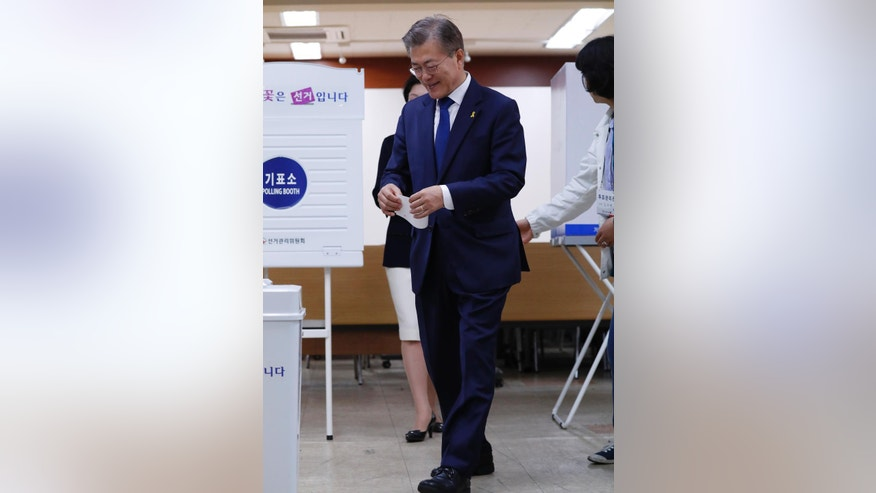 South Korean presidential candidate Moon Jae-in of the Democratic Party walks to cast his ballot for a presidential election at a junior high school in Seoul, South Korea, Tuesday, May 9, 2017. South Koreans voted Tuesday for a new president, with victory widely predicted for a liberal candidate who has pledged to improve ties with North Korea, re-examine a contentious U.S. missile defense shield and push sweeping economic changes. (Jeon Heon-kyun/Pool Photo via AP)