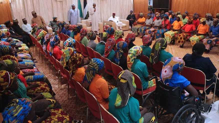 In this photo released by the Nigeria State House, Nigeria's President, Muhammadu Buhari, centre, meets with Chibok school girls recently freed from Nigeria Extremist captivity in Abuja, Nigeria, Sunday, May. 7, 2017. Five Boko Haram commanders were released in exchange for the freedom of 82 Chibok schoolgirls kidnapped by the extremist group three years ago, a Nigerian government official said Sunday, as the girls were expected to meet with the country's president and their families. (Bayo Omoboriowo/Nigeria State House via AP)
