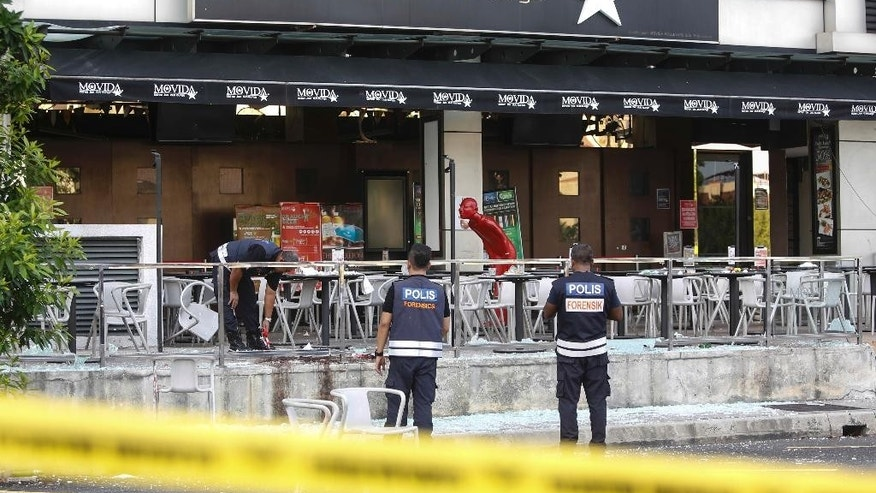 FILE - In this  June 28, 2016, file photo, Malaysian forensic personnel inspect the blast site of a grenade attack at a bar and restaurant in Puchong, outside Kuala Lumpur, Malaysia. Malaysia's police chief said Monday, May 8, 2017, the country's top Islamic State operative was killed in an attack in Syria last month. Muhammad Wanndy Mohamed Jedi, 26, was believed to have been responsible for the grenade blast that injured eight people. It was the first attack in the country by the Islamic State militant group. (AP Photo/Joshua Paul, File)