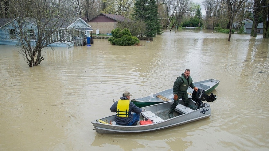Two men move along a flooded street using a small boat in the town of Rigaud, west of Montreal, Sunday, May 7, 2017, following flooding in the region. (Graham Hughes/The Canadian Press via AP)