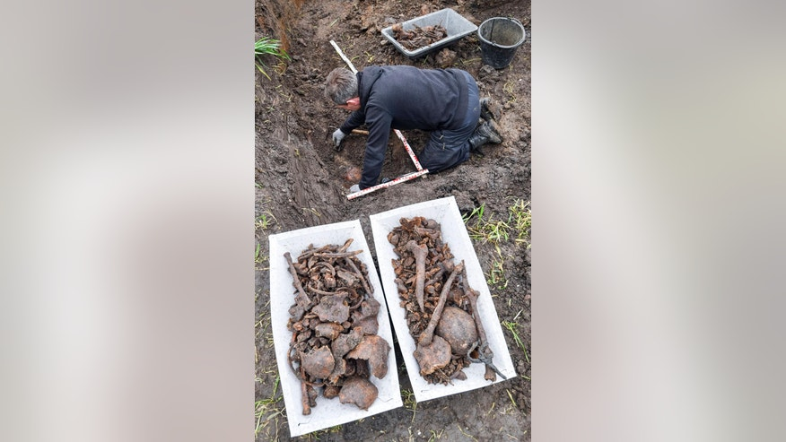 Joachim Kozlowski from the Volksbund charity that takes care of war graves, works at a mass grave in the town of Seelow 70 kilometers (43 miles) east of Berlin, Germany, Monday, May 8, 2017. Seventy-two years after the end of World War II, road workers have found the remains of at least 21 Red Army soldiers. (Patrick Pleul/dpa via AP)