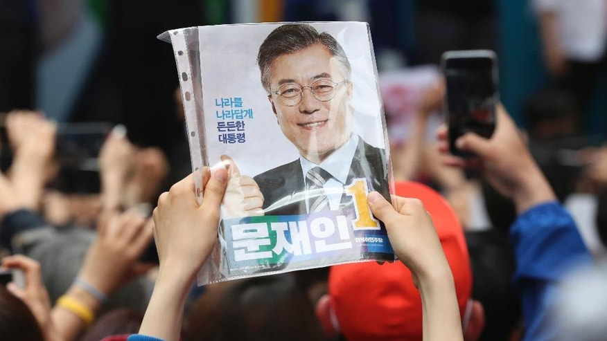 A supporter of South Korea's presidential candidate Moon Jae-in of the Democratic Party holds a leaflet during an election campaign in Busan, South Korea, Monday, May 8, 2017. South Korea's presidential election is scheduled for May 9, 2017. South Korea holds presidential elections Tuesday after an extraordinary six-month period that began with millions peacefully filling the nation's streets in protest and ended with the impeachment and imprisonment of ex-President Park Geun-hye. (AP Photo/Lee Jin-man)