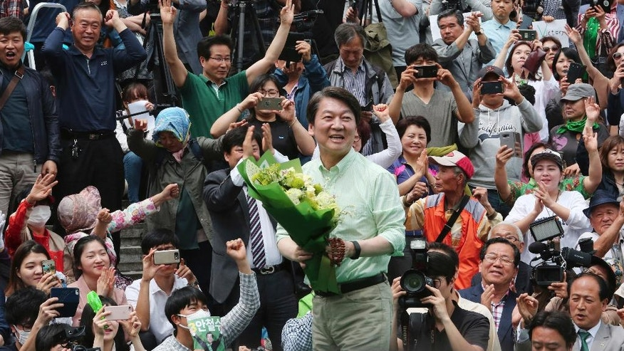 South Korean presidential candidate Ahn Cheol-soo of the People's Party holds flowers in front of supporters during an election campaign in Seoul, South Korea, Monday, May 8, 2017. South Korea holds presidential elections Tuesday after an extraordinary six-month period that began with millions peacefully filling the nation's streets in protest and ended with the impeachment and imprisonment of ex-President Park Geun-hye. (AP Photo/Ahn Young-joon)