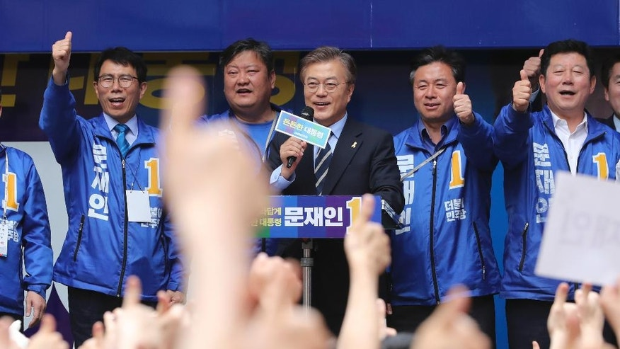 South Korea's presidential candidate Moon Jae-in of the Democratic Party, center, speaks during an election campaign in Busan, South Korea, Monday, May 8, 2017. South Korea's presidential election is scheduled for May 9, 2017. South Korea holds presidential elections Tuesday after an extraordinary six-month period that began with millions peacefully filling the nation's streets in protest and ended with the impeachment and imprisonment of ex-President Park Geun-hye. (AP Photo/Lee Jin-man)