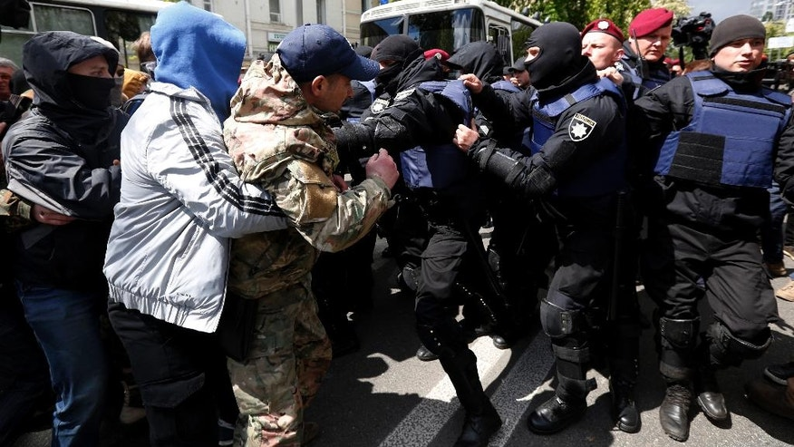 Riot police clash with nationalist activists in Kiev, Ukraine, Tuesday, May 9, 2017. Nationalists blocked pro-Russian groups at a rally to mark Victory Day. Ukrainians mark the anniversary of the victory of World War II on May 9 as a national holiday. (AP Photo/Sergei Chuzavkov)