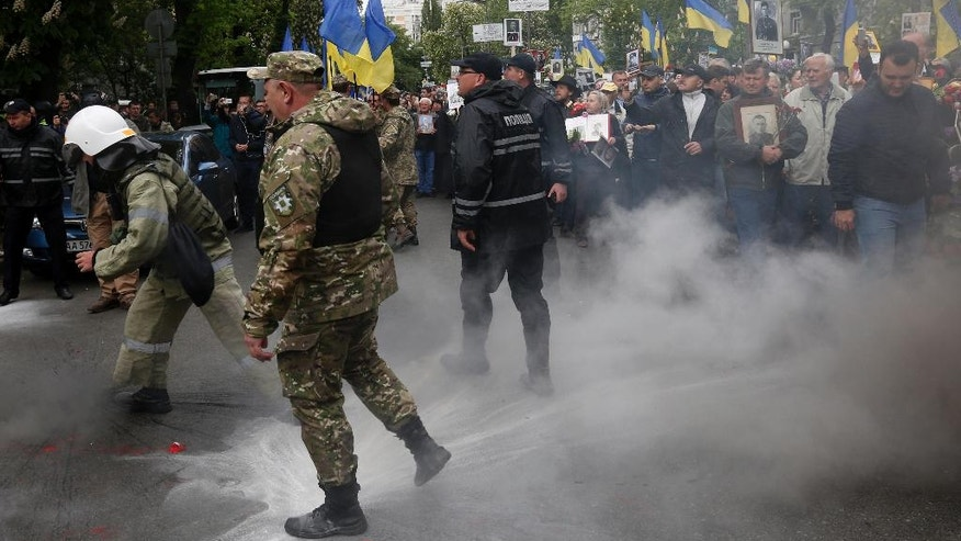 Nationalist activists throw smoke grenades towards pro-Russian groups at a rally to mark Victory Day in Kiev, Ukraine, Tuesday, May 9, 2017 .Ukrainians mark the anniversary of the victory of World War II on May 9 as a national holiday.  (AP Photo/Sergei Chuzavkov)