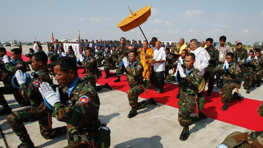 FILE - In this April 7, 2015, file photo, Cambodian Buddhist monks, center, sprinkle holy water onto soldiers during a send-off ceremony inside the Royal Cambodian Air Force in Phnom Penh, Cambodia for military personnel to participate in the United Nations mission in Mali and South Sudan in Africa. Attackers in Central African Republic, the western neighbor nation of South Sudan, ambushed a convoy of U.N. peacekeepers, killing one Cambodian soldier and wounding another, Cambodia's prime minister said Tuesday, May 9, 2017. (AP Photo/Heng Sinith, File)