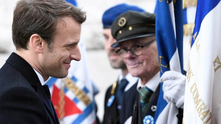 French President-elect Emmanuel Macron smiles to veterans during a ceremony to mark the end of World War II at the Arc de Triomphe in Paris, Monday, May 8, 2017. Macron defeated far-right leader Marine Le Pen handily in Sunday's presidential vote, and now must pull together a majority for his year-old political movement by mid-June legislative elections. (Stephane de Sakutin, Pool via AP)