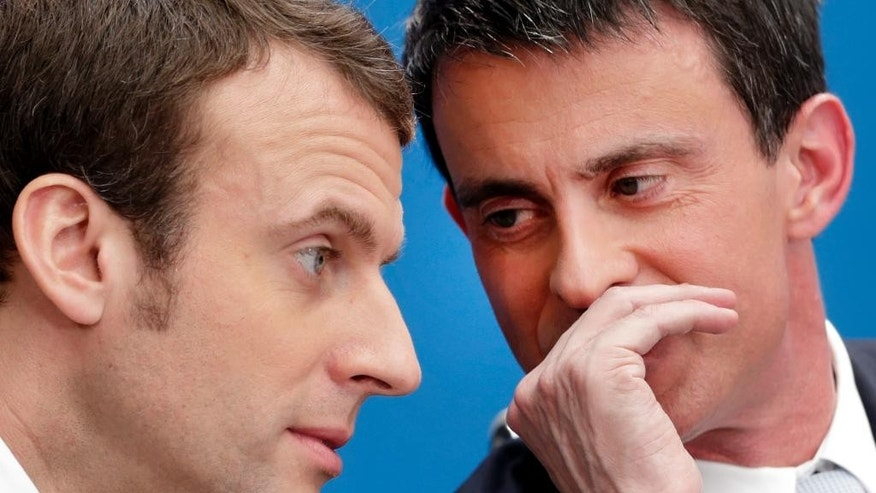 FILE - In this April 8, 2015 file photo, then French prime minister Manuel Valls, right, speaks with then economy minister Macron during in Paris. Valls suggested Tuesday May 9, 2017 that he wants to abandon France's Socialist party and run in June parliamentary elections under the banner of the president-elect's centrist political movement Macron. But it's not clear if he will be able to do so. (AP Photo/Philippe Wojazer/Pool, File)