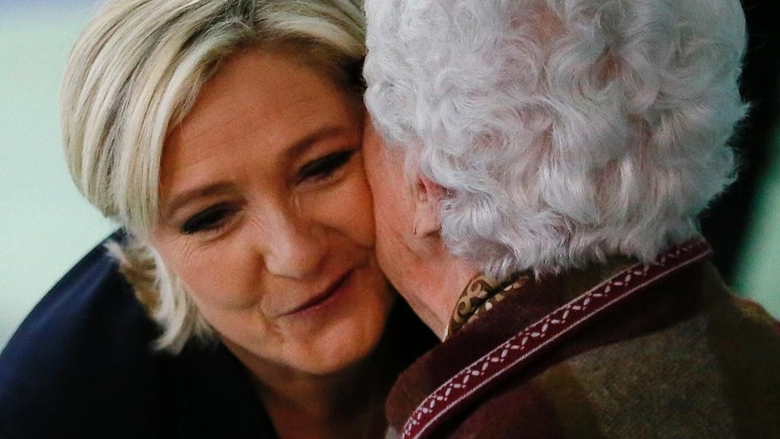 French far-right presidential candidate, Marine Le Pen is greeted after casting her ballot in Henin Beaumont, France, Sunday, May 7, 2017. Voters across France are choosing a new president in an unusually tense and important election that could decide Europe's future, making a stark choice between pro-business progressive Emmanuel Macron and far-right populist Marine Le Pen. (AP Photo/Francois Mori)