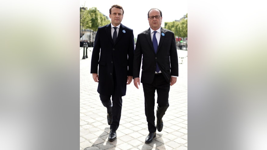 French President-elect Emmanuel Macron, left, and outgoing President Francois Hollande, attend a ceremony to mark the end of World War II at the Arc de Triomphe in Paris, Monday, May 8, 2017. Macron defeated far-right leader Marine Le Pen handily in Sunday's presidential vote, and now must pull together a majority for his year-old political movement by mid-June legislative elections. (Stephane de Sakutin, Pool via AP)