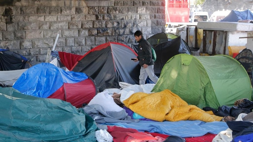An afghan migrant walk trough a evacuated makeshift in Paris, France, Tuesday, May 9, 2017. Paris police have evacuated a makeshift camp of more than 1,000 migrants living in squalid conditions in a northern neighborhood of the French capital. (AP Photo/Michel Euler)