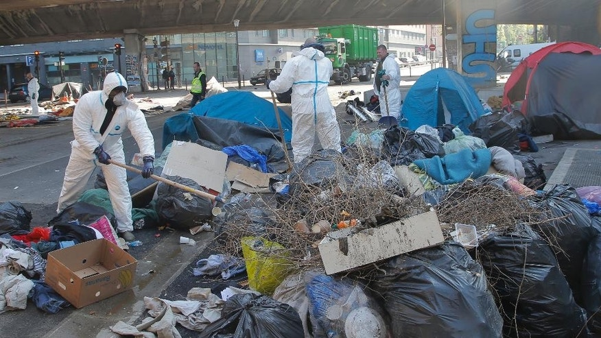 Municipality workers dismante a makeshift camp in Paris, France, Tuesday, May 9, 2017. Paris police have evacuated a makeshift camp of more than 1,000 migrants living in squalid conditions in a northern neighborhood of the French capital. (AP Photo/Michel Euler)