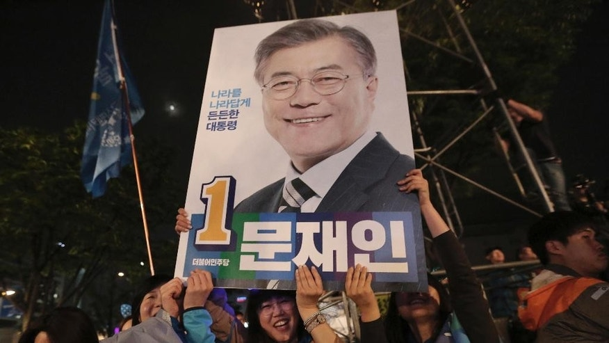 "Supporters of South Korea's presidential candidate Moon Jae-in of the Democratic Party hold up his election poster in Seoul, South Korea, Tuesday, May 9, 2017. Exit polls forecast that liberal candidate Moon will win the election Tuesday to succeed ousted President Park Geun-hye. Official results weren't expected for hours, but the exit poll of about 89,000 voters at 330 polling stations, jointly commissioned by three major television stations and released just after polls closed, showed Moon receiving 41.4 percent of the vote. The sign read ""Moon Jae-in"".(AP Photo/Ahn Young-joon)"