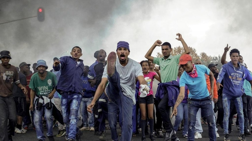 Protesters sing and chant in front of a burning barricade in the Ennerdale, Johannesburg township, Tuesday May 9, 2017. Violent protests have erupted in South Africa's biggest city for a second day, with police firing rubber bullets at demonstrators who blocked roads and burned tires. (AP Photo)