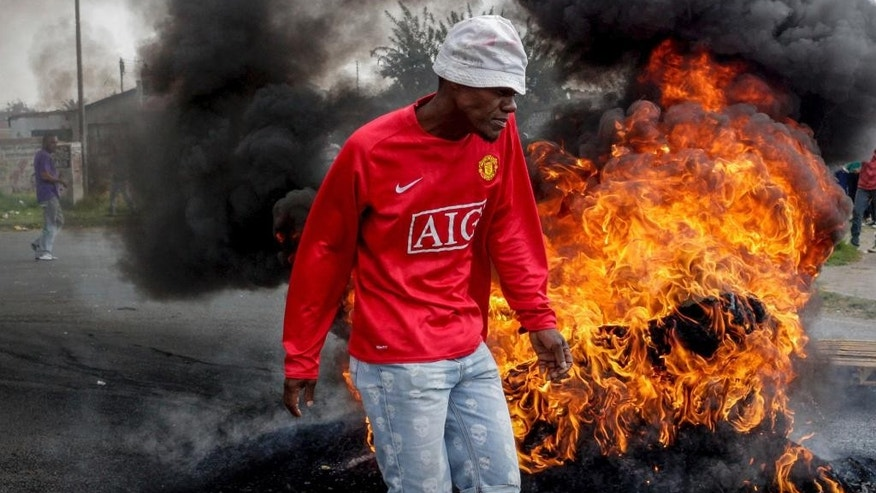 A protester passes a burning barricade in the Ennerdale, Johannesburg township, Tuesday May 9, 2017. Violent protests have erupted in South Africa's biggest city for a second day, with police firing rubber bullets at demonstrators who blocked roads and burned tires. (AP Photo)