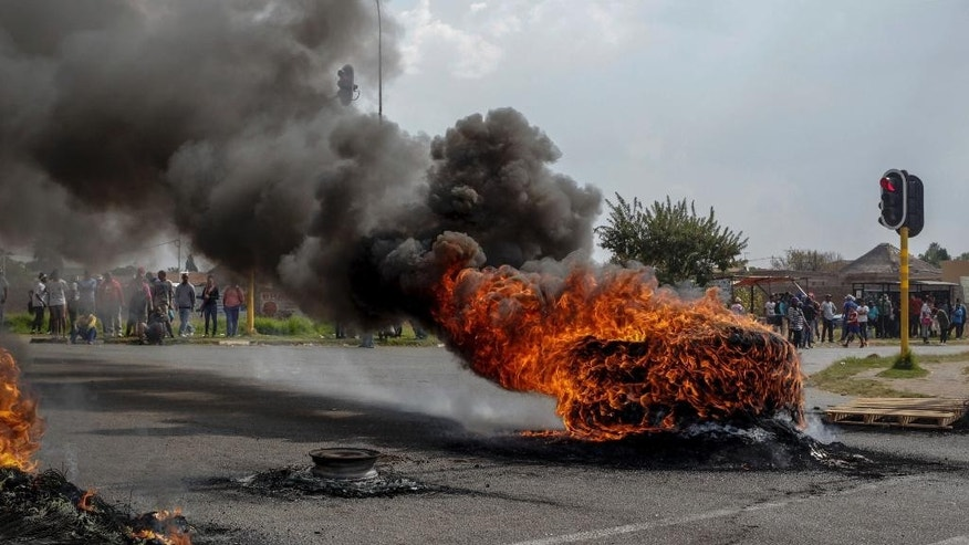 Protesters stand behind burning barricades in the Ennerdale, Johannesburg township, Tuesday May 9, 2017. Violent protests have erupted in South Africa's biggest city for a second day, with police firing rubber bullets at demonstrators who blocked roads and burned tires. (AP Photo)
