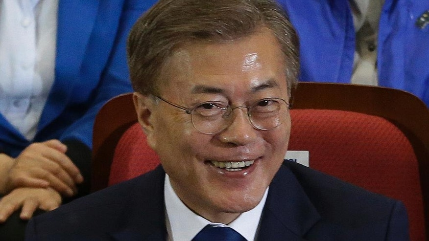 South Korea's presidential candidate Moon Jae-in of the Democratic Party smiles as he along with his party leaders and members watch the local media's results of exit polls for the presidential election on television in Seoul, South Korea, Tuesday, May 9, 2017. Exit polls forecast that liberal candidate Moon will win the election Tuesday to succeed ousted President Park Geun-hye. (AP Photo/Ahn Young-joon)