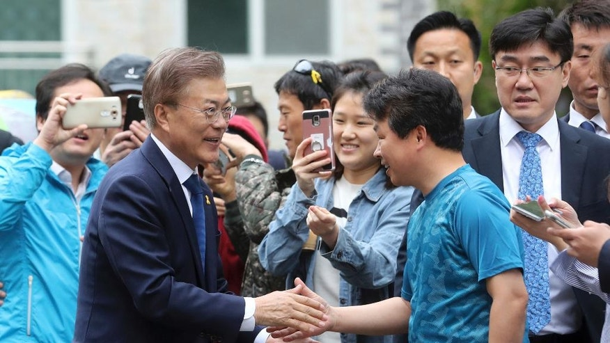 South Korean presidential candidate Moon Jae-in, front left, of the Democratic Party shakes hands with a supporter after voting for a presidential election at a junior high school in Seoul, South Korea, Tuesday, May 9, 2017. South Koreans voted Tuesday for a new president, with victory widely predicted for a liberal candidate who has pledged to improve ties with North Korea, re-examine a contentious U.S. missile defense shield and push sweeping economic changes. (Choe Jae-koo/Yonhap via AP)