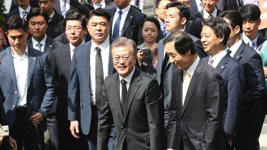 Newly elected South Korean President Moon Jae-in, center, leaves his house in Seoul, South Korea, Wednesday, May 10, 2017. Hours after celebrating his election win with thousands of supporters in wet Seoul streets, new South Korean President Moon on Wednesday was quickly thrown into the job of navigating a nation deeply split over its future and faced with growing threats from North Korea and an uneasy alliance with the United States. (AP Photo/Lee Jin-man)