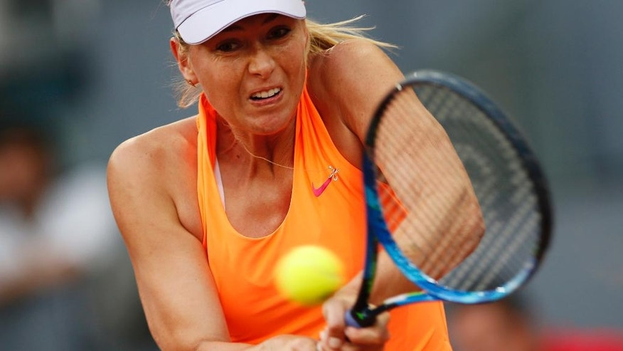 Maria Sharapova from Russia returns a ball to Eugenie Bouchard from Canada during a Madrid Open tennis tournament match in Madrid, Spain, Monday, May 8, 2017. Bouchard won 7-5, 2-6 and 6-4. (AP Photo/Francisco Seco)