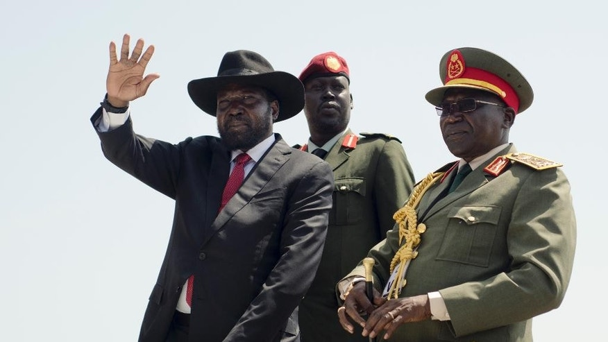 FILE - In this Thursday, July 9, 2015 file photo, South Sudan's President Salva Kiir, left, accompanied by army chief of staff Paul Malong, right, waves during an independence day ceremony in the capital Juba, South Sudan.  South Sudan's army chief of staff Paul Malong, who had been proposed for U.N. sanctions and accused of directing last year's fighting in the capital that left hundreds dead, has been removed from his post, a presidential spokesman said Tuesday, May 9, 2017. (AP Photo/Jason Patinkin, File)