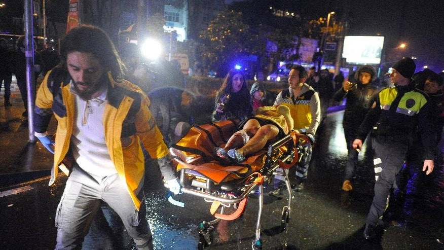 FILE-In this early Sunday, Jan. 1, 2017 file photo, Medics carry a wounded person at the scene after an attack at a popular nightclub in Istanbul. Turkey's state-run news agency said on tuesday, May 9, 2017, prosecutors in Istanbul are demanding 40 consecutive life sentences for the man who attacked the nightclub, killing 39 people. (IHA via AP, File)