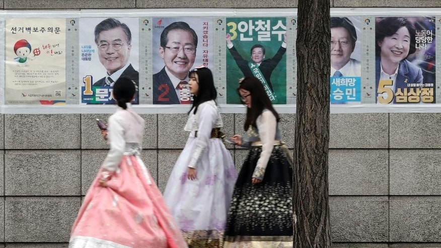 Women walk by posters showing candidates for the presidential election in Seoul, South Korea, Tuesday, May 9, 2017. South Koreans voted Tuesday for a new president, with victory widely predicted for a liberal candidate who has pledged to improve ties with North Korea, re-examine a contentious U.S. missile defense shield and push sweeping economic changes. (AP Photo/Lee Jin-man)