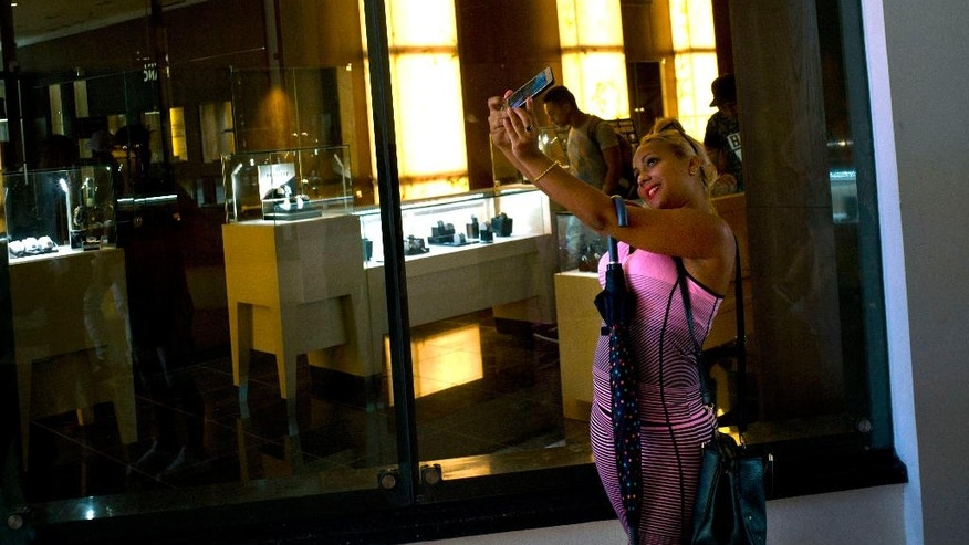 A Cuban girl takes a selfie in front of a window of a luxury store at the Manzana de Gomez Kempinski five-star hotel in Havana, Cuba, Monday, May 8, 2017. With other sectors declining, Cuba's increasingly important tourism industry is under pressure to change its state-run hotels' reputation for charging exorbitant prices for rooms and food far below international standards. The Manzana de Gomez Kempinski bills itself as Cuba's first real five-star hotel, and the brand-name shops around it appear designed to reinforce that. (AP Photo/Ramon Espinosa)