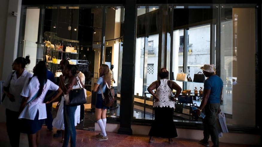 People look at the storefront window of a luxury store at the Manzana de Gomez Kempinski five-star hotel in Havana, Cuba, Monday, May 8, 2017. The hotel is earning positive early reviews but many tourists say they find the luxury mall alongside it to be repulsive. (AP Photo/Ramon Espinosa)