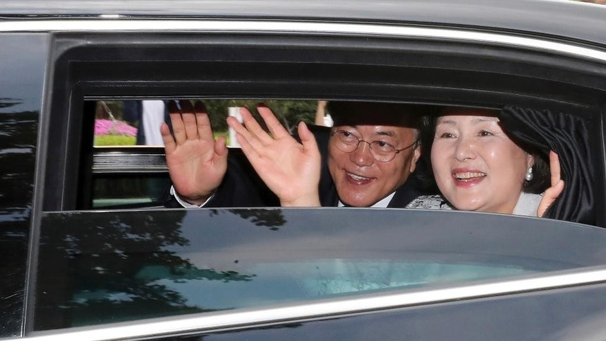 South Korean President Moon Jae-in and his wife Kim Jung-sook wave to people as they move to the presidential Blue House after his inauguration ceremony in Seoul, South Korea, Wednesday, May 10, 2017. Moon said Wednesday he was open to visiting rival North Korea under the right conditions to talk about Pyongyang's aggressive pursuit of nuclear-tipped missiles. (Baek Seung-ryul/Yonhap via AP)