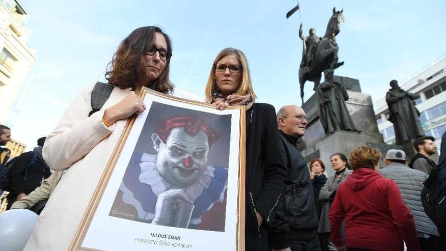 Demonstrators hold a cartoon of Czech President Milos Zeman as a clown as they take part in a protest at Prague's Wenceslas Square, Wednesday, May 10, 2017. Tens of thousands of people are rallying in the Czech Republic's capital and other major cities demanding Finance Minister Andrej Babis' firing and Zeman's resignation. (Katerina Sulova/ CTK via AP)