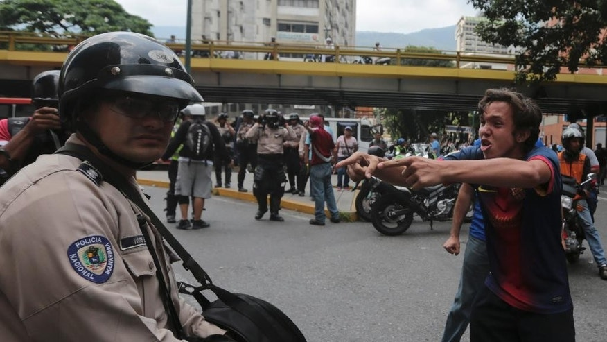 An anti-government protester shouts at a police officer in downtown Caracas, Venezuela, Wednesday, May 10, 2017. Opponents of President Nicolas Maduro will attempt to march to the Supreme Court to protest its decision to gut the opposition-controlled congress of its powers, a ruling that was quickly rescinded under a barrage of international criticism but that set off weeks of political unrest that have left some three dozens killed. (AP Photo/Fernando Llano)