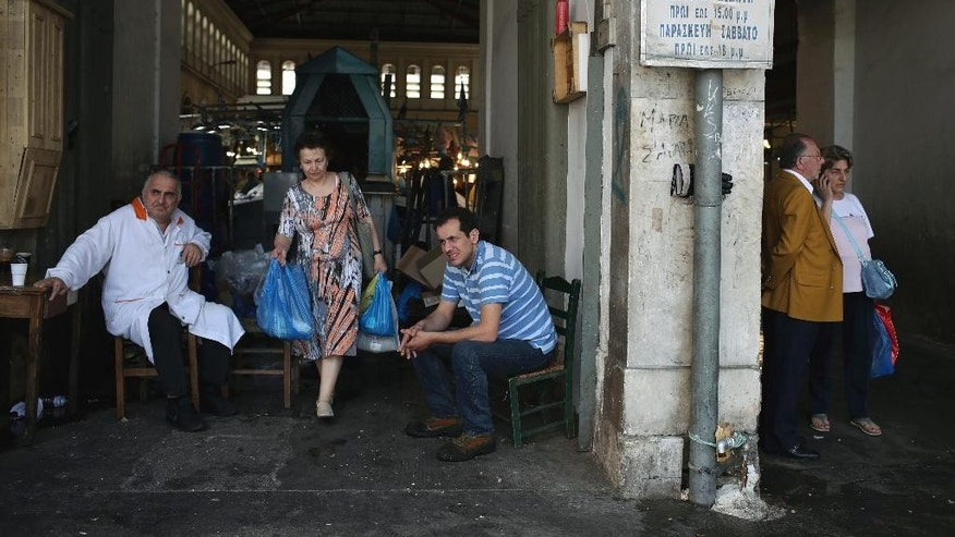 A woman carries bags as she leaves the Athens's central fish market as workers take a break, in Athens, Wednesday, May 10, 2017. Greece has been surviving on bailout loans since 2010 in return for harsh spending cuts and tax increases that have put nearly a quarter of the workforce out of work and seen more than a third of the population living  or at risk of poverty. (AP Photo/Petros Giannakouris)