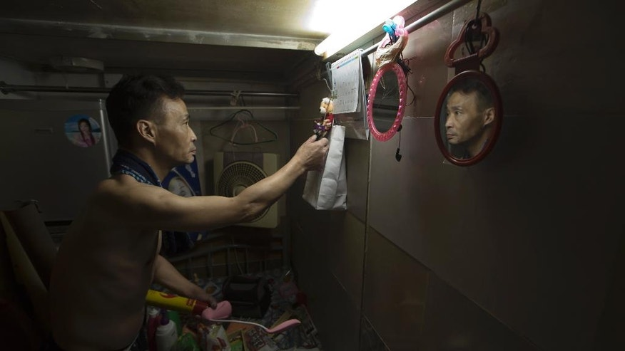 "In this Thursday, May 4, 2017 photo,  a resident who only gave his surname Sin, 55, tidies up the bed in his ""coffin home"" in Hong Kong. In wealthy Hong Kong, there's a dark side to a housing boom, with hundreds of thousands of people forced to live in partitioned shoebox apartments, ""coffin homes"" and other ""inadequate housing.(AP Photo/Kin Cheung)"