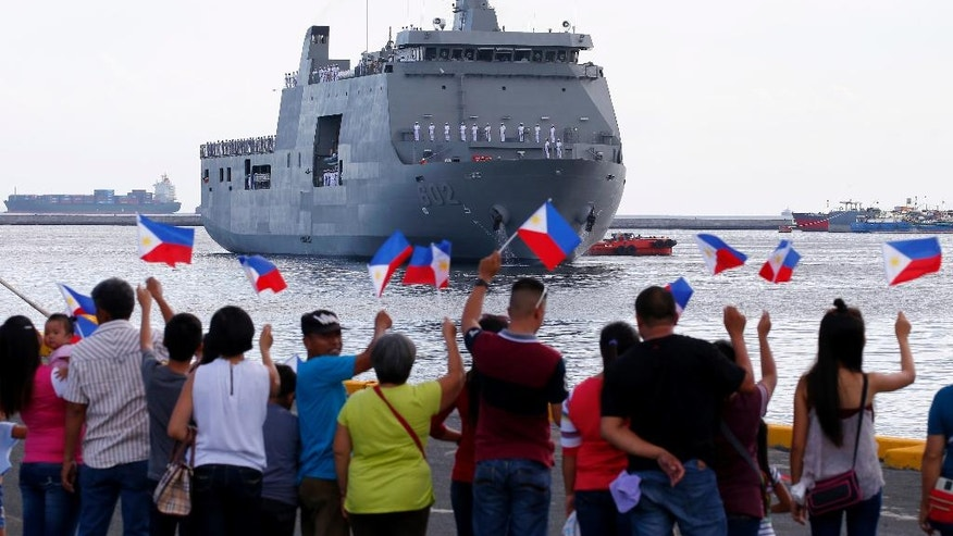 Families of Philippine navy crew wave their country flags to welcome its new ship named BRP Davao del Sur at Manila's South Harbor for a ceremony to be led by Rear Adm. Gaudencio Collado Jr., commander of the Philippine Fleet Wednesday, May 10, 2017 in Manila, Philippines. The Philippine navy welcomed Wednesday the second Indonesian-made amphibious landing dock as part of the military's modernization program. (AP Photo/Bullit Marquez)