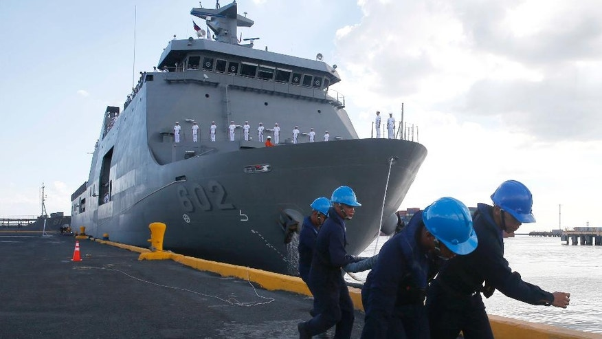 Philippine navy crew pull a rope as its new ship named BRP Davao del Sur is docked at Manila's South Harbor for a ceremony to be led by Rear Adm. Gaudencio Collado Jr., commander of the Philippine Fleet Wednesday, May 10, 2017 in Manila, Philippines. The Philippine navy welcomed Wednesday the second Indonesian-made amphibious landing dock as part of the military's modernization program. (AP Photo/Bullit Marquez)