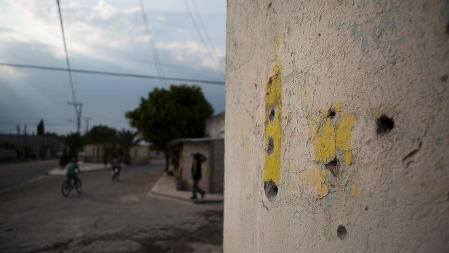 Bullet holes mark a wall at an intersection where a video released by Mexican media outlets appeared to show a soldier executing a civilian lying face down in the street with a shot to the back of his head, in Palmarito Tochapan, Puebla State, Wednesday, May 10, 2017. The footage purportedly depicts a portion of the military's encounter with fuel pipeline thieves in that the government said left 10 dead. (AP Photo/Rebecca Blackwell)