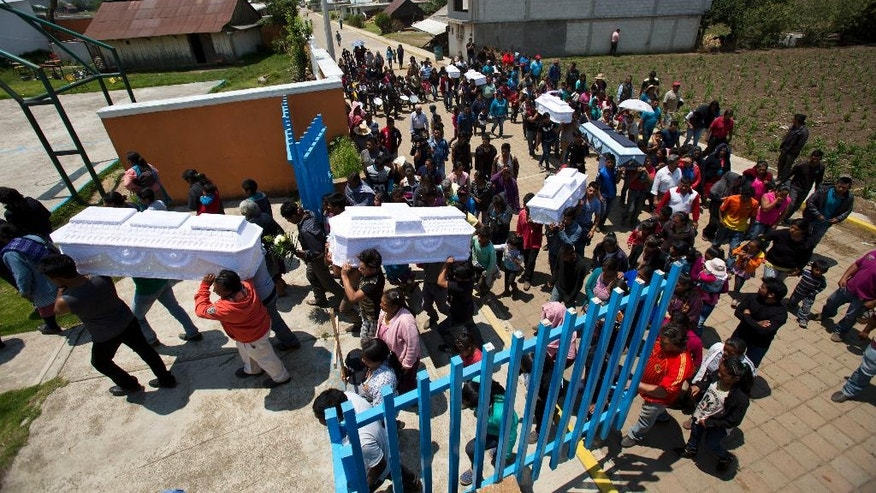 Coffins containing the remains of seven children killed in a fireworks explosion are carried into the grounds of the local school as family and community join to pay their final respects, in San Isidro, Mexico, Wednesday, May 10, 2017. An errant firecracker landed on a cache of fireworks and touched off a powerful explosion Tuesday, at a home in the Mexican state of Puebla, killing 11 children and three adults. (AP Photo/Rebecca Blackwell)