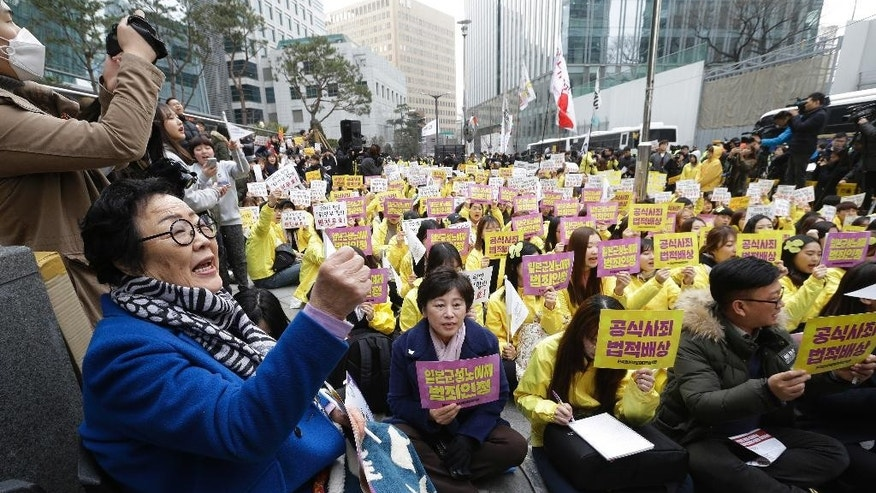 "FILE - In this March 1, 2017, file photo, former ""comfort woman"" Lee Yong-soo, left bottom, who was forced to serve for the Japanese troops as a sex slave during World War II, shouts slogans during a rally to mark the March First Independence Movement Day, the anniversary of the 1919 uprising against Japanese colonial rule, near the Japanese Embassy in Seoul, South Korea. Japan is particularly concerned about the ""comfort women"" issue, a legacy of Japanese atrocities during the war that still haunts relations between the two sides. South Korea's new President Moon Jae-in opposes a 2015 agreement signed by Park Geun-hye that was heralded as a final settlement for Korean women who were among many sexually enslaved in Japanese military brothels before and during World War II. Moon has called for a renegotiation of the pact. The signs read: ""Apology and Compensation."" (AP Photo/Ahn Young-joon, File)"