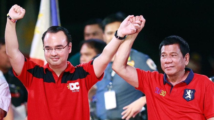 FILE - In this May 7, 2016, file photo, Sen. Alan Peter Cayetano, left, running mate of then front-running presidential candidate Mayor Rodrigo Duterte raise hands during their final campaign rally in Manila, Philippines. Duterte told reporters Wednesday, May 10, 2017, before flying to Cambodia to attend the World Economic Forum on ASEAN that he had appointed Cayetano as the country's new foreign secretary. (AP Photo/Aaron Favila, File)