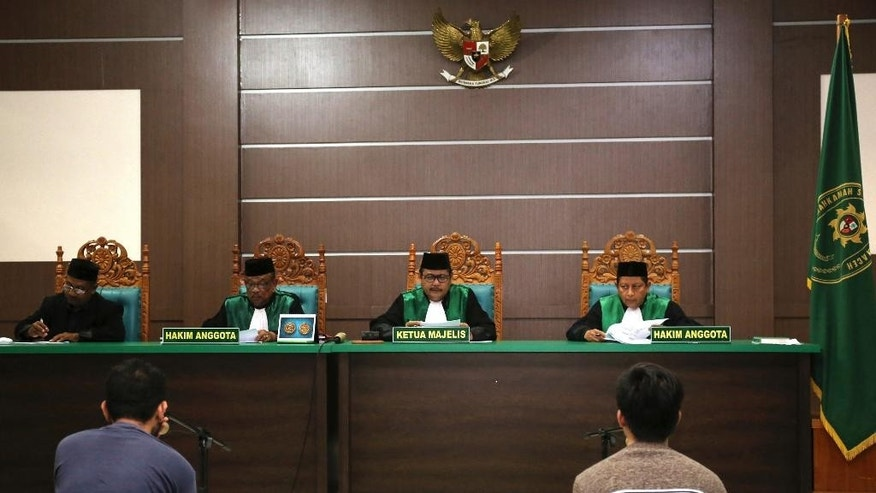 Two men accused of having gay sex sit on the defendants' chairs during their trial at Shariah court in Banda Aceh, Indonesia, Wednesday, May 10, 2017. Shariah prosecutors in Aceh province said the two men should each receive 80 lashes, in another blow to the country's moderate image after a top Christian official was imprisoned for blasphemy. (AP Photo/Heri Juanda)