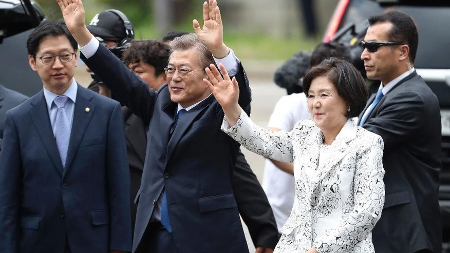 South Korea's new President Moon Jae-in waves to neighborhoods and supporters with his wife Kim Jung-sook upon their arrival outside the presidential Blue House in Seoul, South Korea, Wednesday, May 10, 2017. Moon said Wednesday he was open to visiting rival North Korea under the right conditions to talk about Pyongyang's aggressive pursuit of nuclear-tipped missiles. (AP Photo/Lee Jin-man)