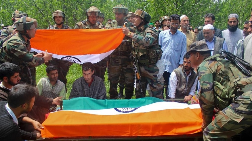 Indian army soldiers cover the coffin of their colleague Umar Fayaz with Indian flag during his funeral at Sursoona village, 80 kilometers (50 miles) south of Srinagar, Indian controlled Kashmir, Wednesday, May 10, 2017. Kashmiri militants kidnapped and shot dead the Indian army officer who was visiting home in the disputed Himalayan region, the Indian military said Wednesday. (AP Photo/Sajad Muniward)