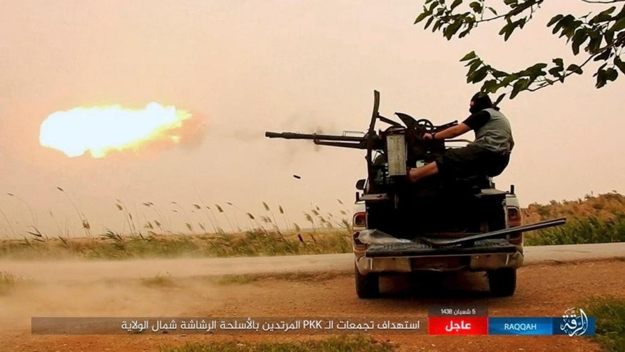 "FILE -- This undated image posted online Monday, May 1, 2017, by supporters of the Islamic State militant group on an anonymous photo sharing website, purports to show an Islamic State fighter firing his weapon during clashes with U.S.-backed Kurdish-led Syrian Democratic Forces, in the northern Syrian province of Raqqa. A top Syrian Kurdish official said Wednesday, May 10, 2017, that the U.S. decision to arm Kurdish fighters with heavier weapons will help legitimize the force, which is denounced as a terrorist organization by Turkey. The Trump administration announced Tuesday it will arm the Kurdish-led Syrian Democratic Forces ""as necessary"" to recapture the Islamic State stronghold of Raqqa. (Militant Photo via AP)"